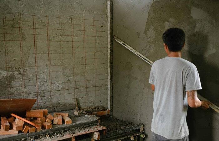 Homem impermeabilizando parede